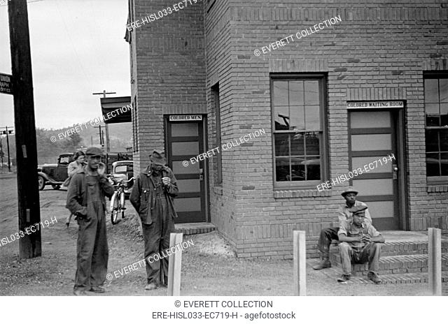 Colored Waiting Room sign. Four African American men stand outside of the Manchester, Georgia, railroad station. May 1938