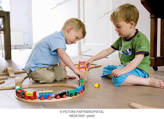 Two little boys playing with a wooden train