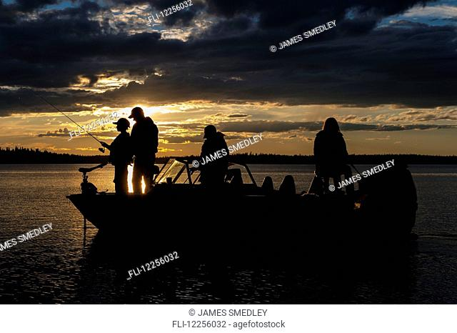 Silhouette of a family fishing from their motorboat on a lake at sunset in Northern Ontario; Ontario, Canada