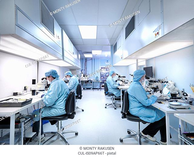 Electronics workers in clean room assembling electronic components