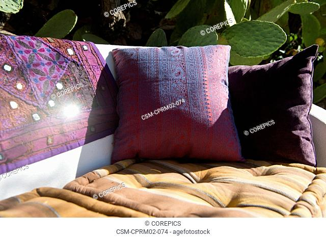 Pillows and drapes on a bench