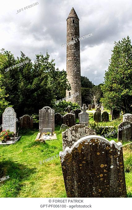 GRAVESTONES IN FRONT OF THE 33-METER HIGH ROUND TOWER, RUINS OF THE OLD MONASTERY OF GLENDALOUGH FOUNDED IN THE 6TH CENTURY AND DESTROYED IN 1398 BY THE ENGLISH
