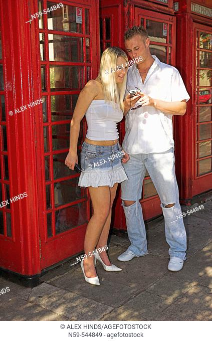 Young couple using mobile phones on street next to row of British public phone boxes