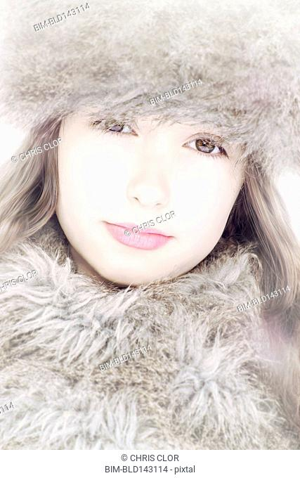 Close up of Caucasian girl wearing fur hat and scarf