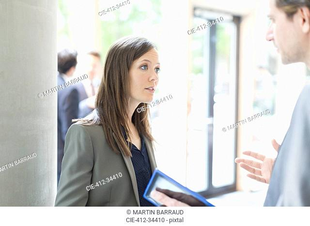 Serious businesswoman listening to businessman with digital tablet in office lobby