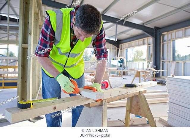 Close-up of carpenter wearing hi viz measuring cut mark on wood on building construction site interior