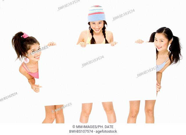 Three pretty teens holding a large blank white sign