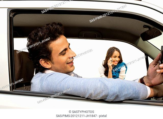 Man sitting in a car with his girlfriend talking on mobile phone in background