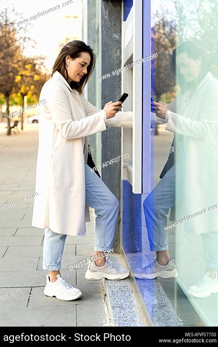 Stylish female entrepreneur using smart phone while withdrawing money from ATM