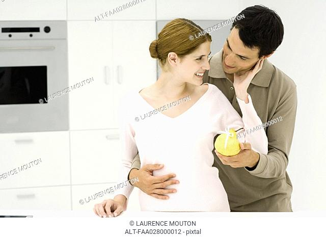 Man giving woman pear tied with ribbon, both smiling
