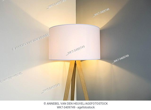 floor lamp standing near white grey wall with big lamp shade modern design, symmetrical light background texture close-up