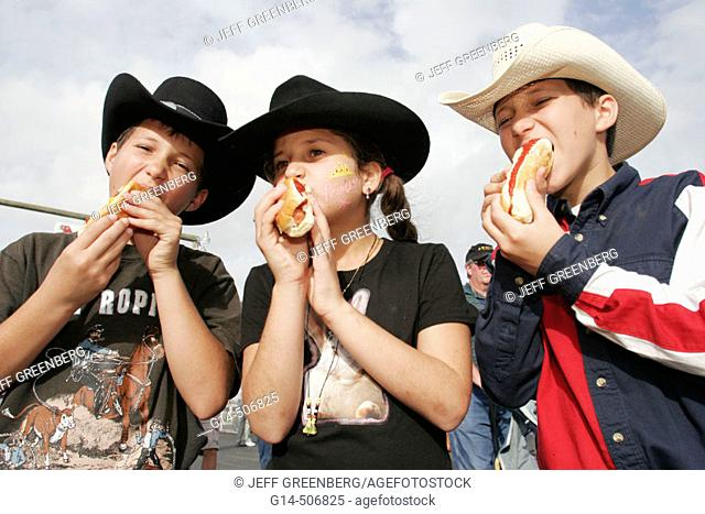 Boys, girl, hot dog, eat, bite, bun, cowboy hat. Championship Rodeo. Homestead. Florida. USA