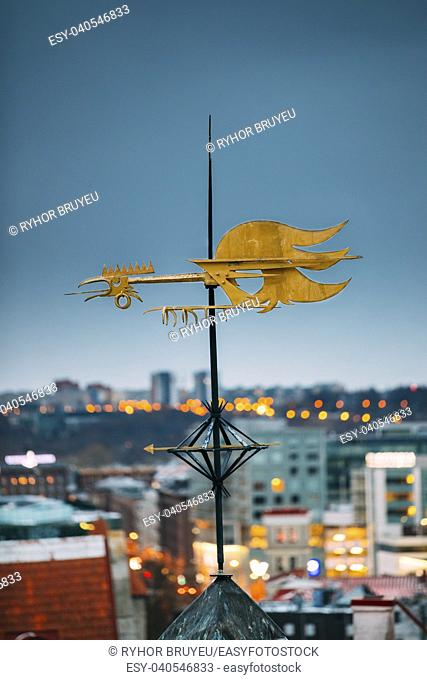 Tallinn, Estonia, Europe. Close Up Of Cock-rope Weather Vane On Roof Of Old Medieval House In Winter Evening In Night Illuminations Lights