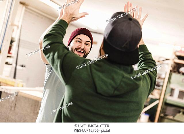 Two happy young men high fiving in workshop