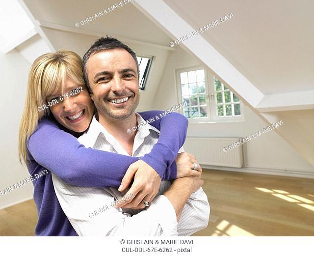 Happy couple in an embrace in empty loft