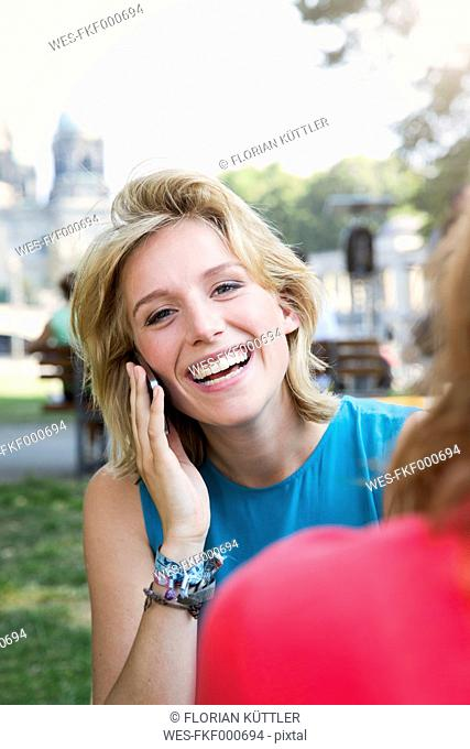 Germany, Berlin, Young woman using smart phone in park