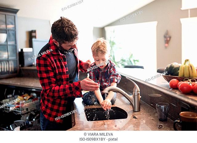Father watching son wash hands in kitchen sink