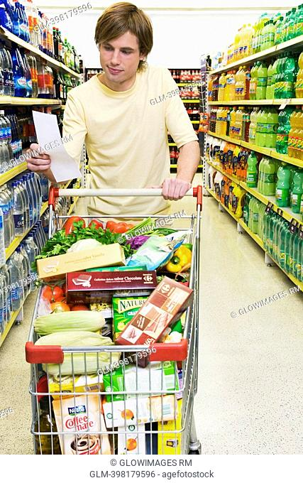 Man with a shopping cart and a shopping list