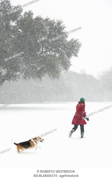 Caucasian woman walking in snow storm with dog