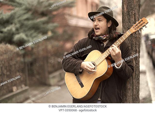 man playing guitar at street in city