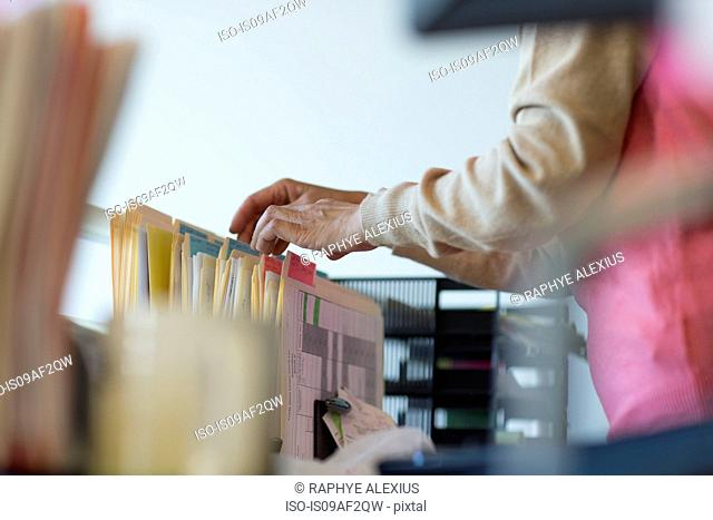 Senior woman looking through filing cabinet