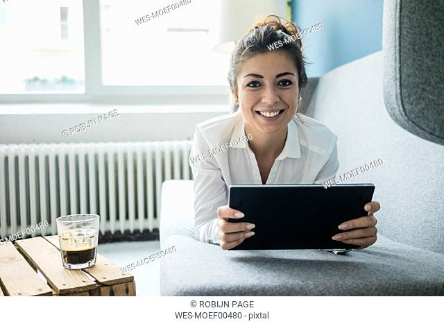 Portrait of laughing woman relaxing on couch with tablet