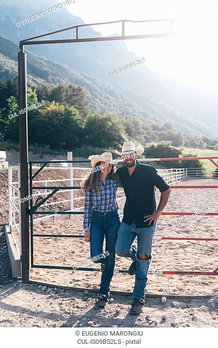 Cowgirl and boyfriend in rural equestrian arena, portrait, Primaluna, Trentino-Alto Adige, Italy