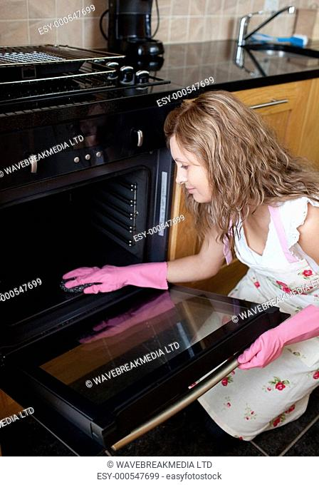 Young woman cleaning the oven in the kitchen