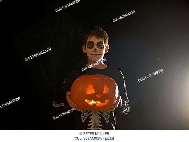 Portrait of boy wearing halloween skeleton costume holding pumpkin