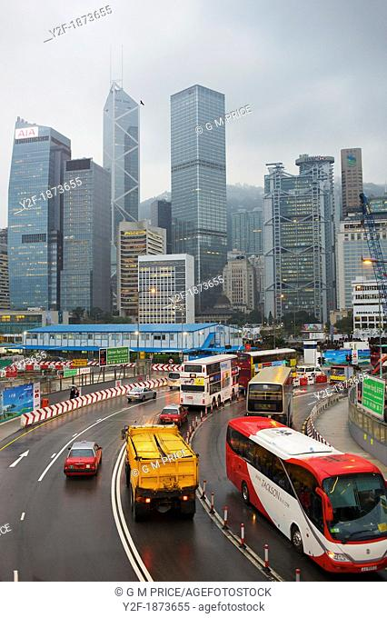 cars, buses and trucks with Hong Kong skyline at Central
