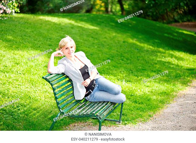 Young woman sitting on bench in park and smiling