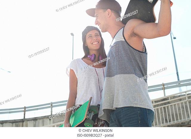 Young couple holding skateboards, Budapest, Hungary