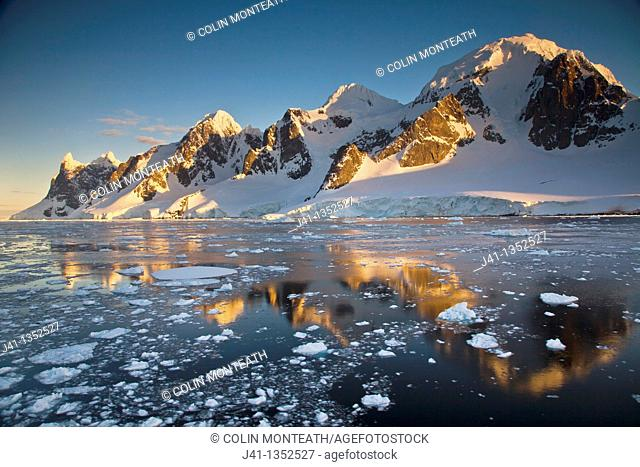 Lemaire Channel reflection at sunset, peaks near Cape Renard, Antarctic Peninsula