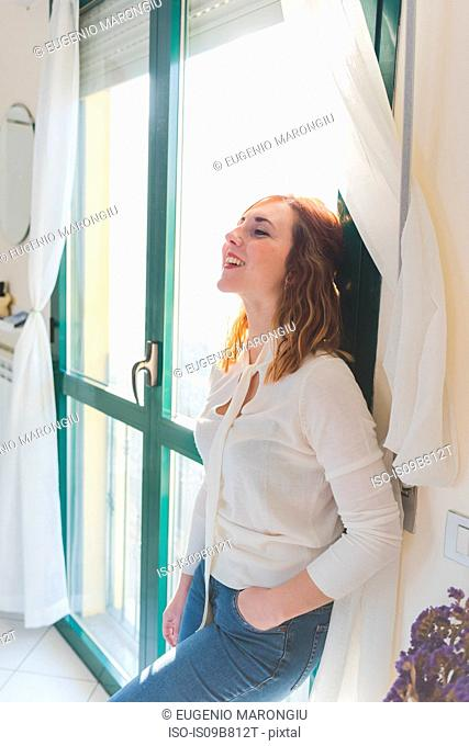Happy young woman leaning against patio door