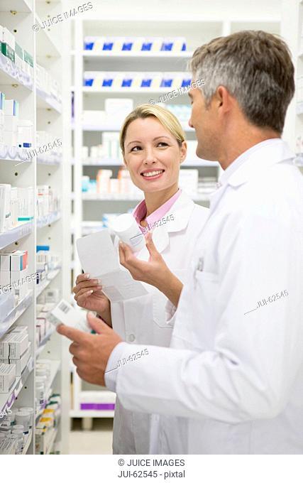 Pharmacists checking bottle of prescription medication on pharmacy shelves