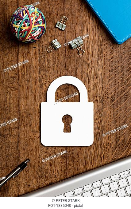 View from above paper padlock on wooden desk