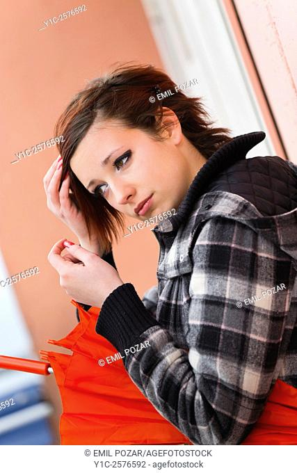 Teenager girl with Red umbrella is adjusting hair