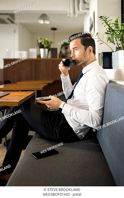 Businessman enjoying coffee and having a break on bench in cafe