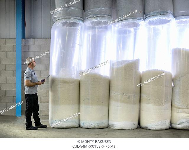 Worker using machinery in textile mill