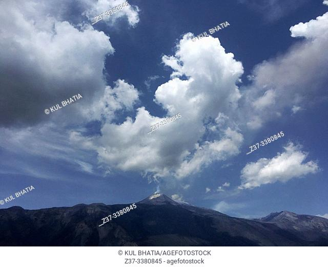 Gases coming out of Mount Etna's active crater seem to merge with the clouds above on a summer day. Lava flows old and new are evident in the different shades...