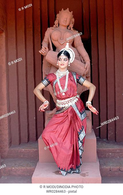 Woman performing classical traditional Odissi dance in front of statue on stage MR736C