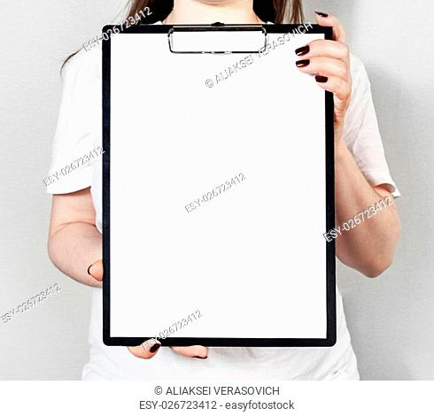 Blank paper in clipboard in female hands. Mock-up for design presentations and portfolios