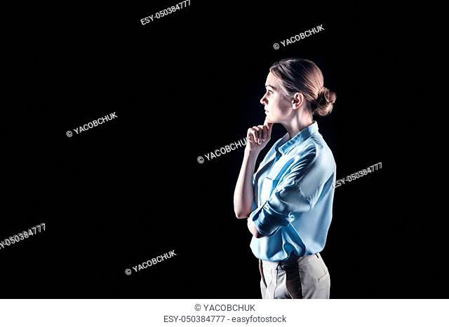 Pensive look. Nice attractive young woman standing and thinking while looking for a solution to the problem