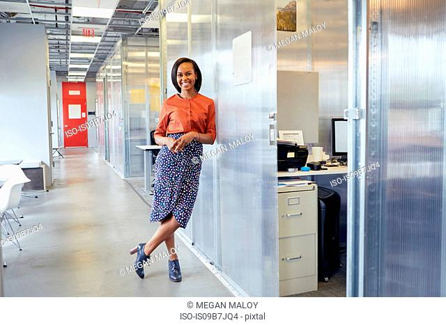 Portrait of businesswoman standing in office corridor, leaning against office surround, smiling