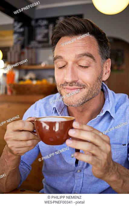 Portrait of smiling man with eyes closed with cup of coffee in a coffee shop