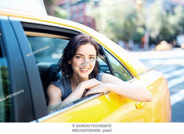 USA, New York City, portrait of smiling young woman sitting inside of yellow cab