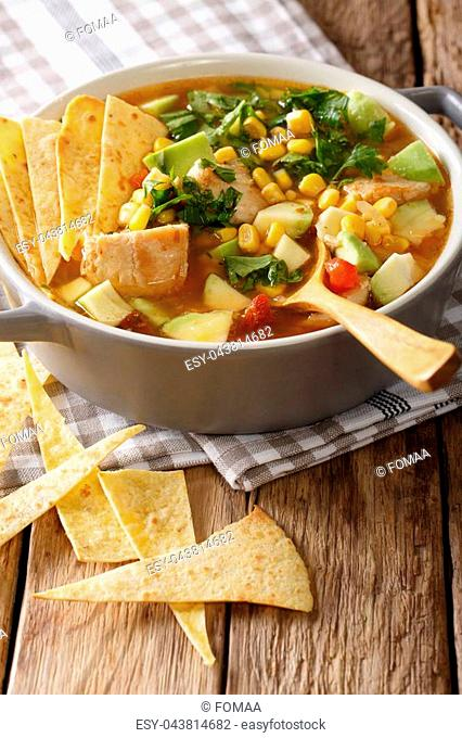 Mexican food: tortilla soup with chicken, tomatoes, avocado and corn close-up in a saucepan on a table. vertical