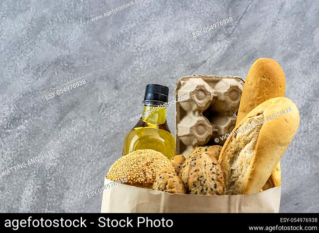 Grocery bag with egg cooking oil and variety of bread in disposalable paper bag on gray vintage loft background. Bakery food and drink and grocery concept for...