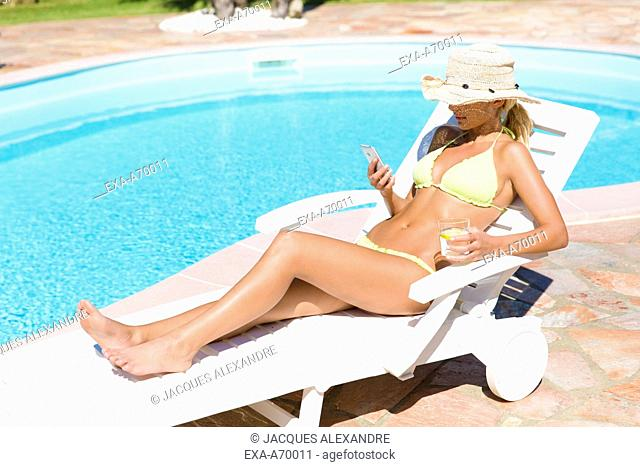 woman lying at pool with mobile phone
