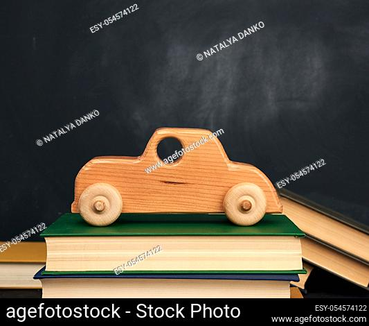 stack of books and wooden toy car on wheels, background from black chalk board, back to school